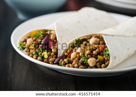 Vegan wraps with lentil, chickpea, kidney bean, peppers and hummus sauce - stock photo