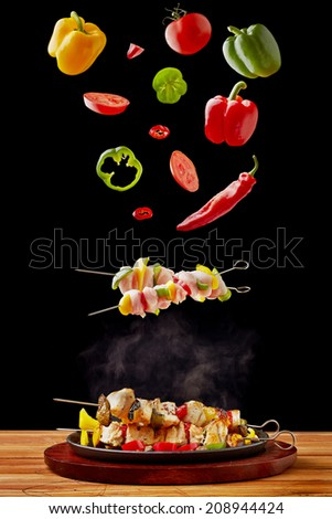 Vegetable and chicken kebab falling into a hot cast iron pan - stock photo