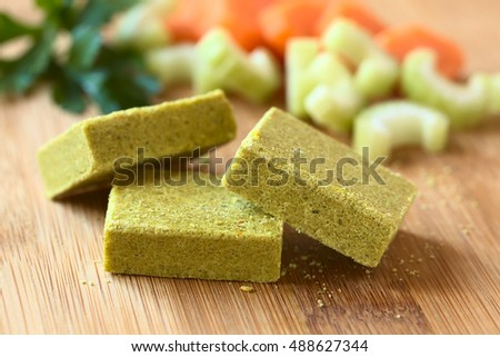 Vegetable bouillon, stock or broth cubes with parsley and fresh celery and carrot in the back, photographed with natural light (Selective Focus, Focus on the upper edge of the two cubes in the front)