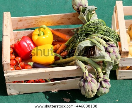 vegetable box with yellow and red peppers and artichokes just harvested from the garden