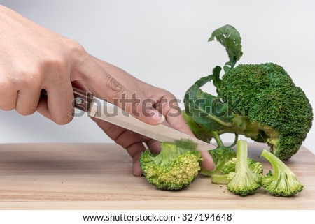 vegetable broccoli with hand holding a knife on white background