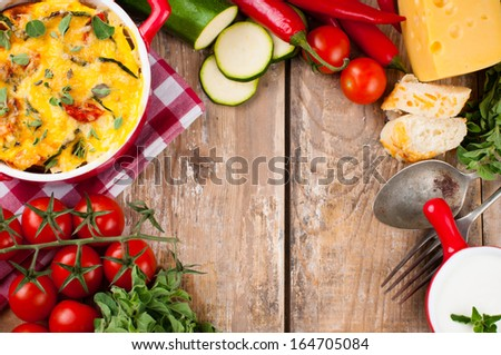 Vegetable casserole in a red pot with cheese, zucchini, cherry tomatoes, oregano and cream sauce on a wooden board, food background, home cooking