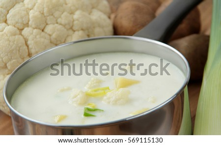Vegetable cauliflower soup in a stainless pot and ingredients - cauliflower, potatoes and leek on wooden table.