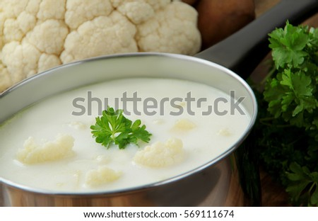 Vegetable cauliflower soup in a stainless pot. Ingredients - cauliflower and parsley on  background.