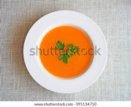 Vegetable cream soup with carrot in white bowl. Top view on a rough white cloth. Healthy diet meal. - stock photo