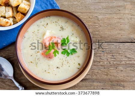 Vegetable cream soup with shrimps and croutons in bowl over wooden background with copy space - stock photo