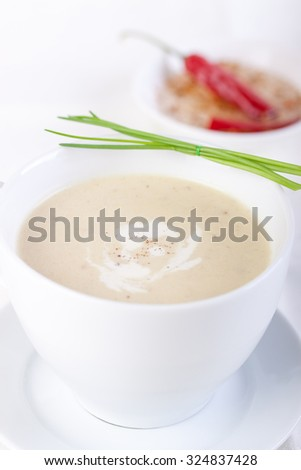 Vegetable creamy soup with cauliflower and cream in a white ceramic bowl
