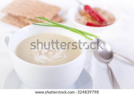 Vegetable creamy soup with cauliflower and cream in a white ceramic bowl  - stock photo