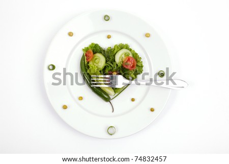 Vegetable dietary composition in the form of heart on a white plate with a plug.