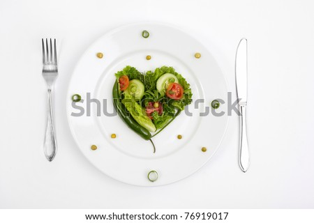 Vegetable dietary composition in the form of heart on a white plate with a plug and a knife. - stock photo
