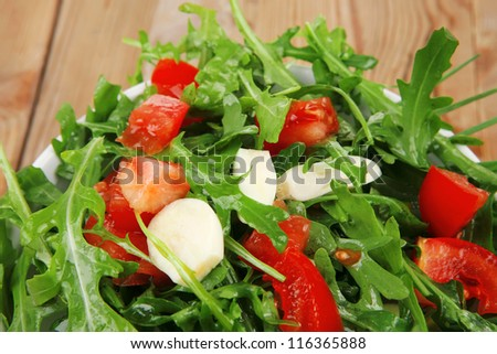 vegetable food : green salad with raw tomato and garlic in white bowl over wood served with cutlery