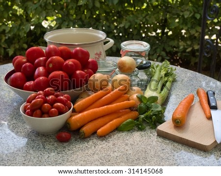 Vegetable ingredients for typical italian tomato sauce contain tomato, onion, carrot, petiolate celery and basil leaves. Seasonal riped vegetables with old fashion preserving jars, cooking pot.  - stock photo