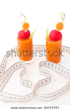 Vegetable juice with tape measure's hearts on white background, concept of healthy food - stock photo