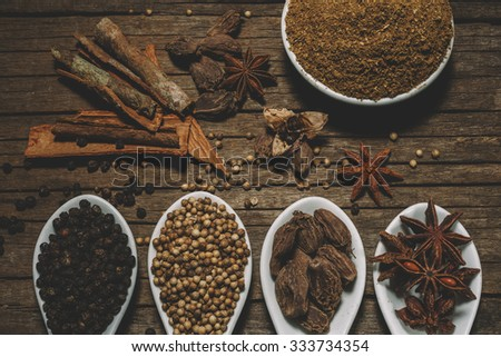 Vegetable masala with selection of spices on wooden spoons - stock photo