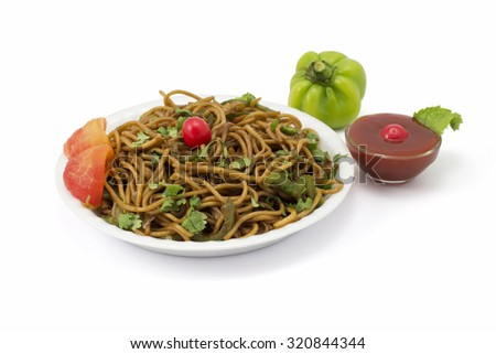 Vegetable Noodles topped with coriander leaves, mint leaves and cherry; served with tomato sauce and capsicum. - stock photo