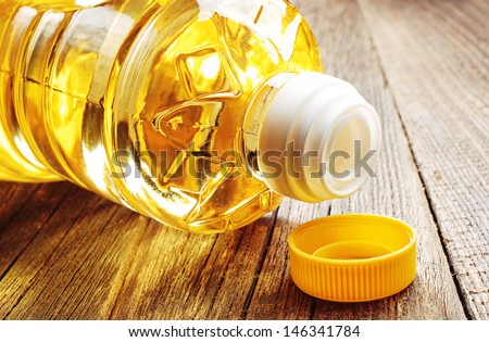 Vegetable oil in plastic bottle closeup on the old wooden table - stock photo