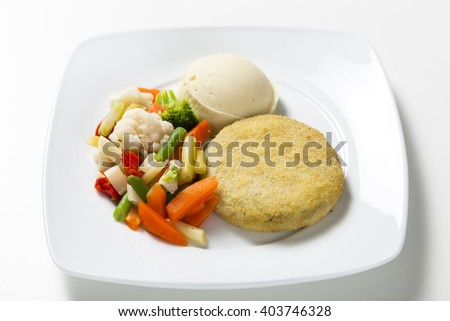 Vegetable patty with vegetables on a white plate - stock photo