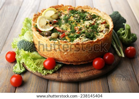 Vegetable pie with broccoli, peas, tomatoes and cheese on wooden background - stock photo