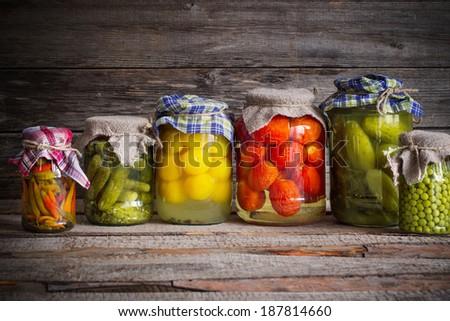 Vegetable preserves on wooden background - stock photo