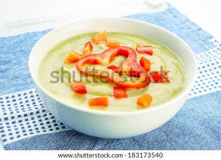 vegetable puree garnished with red pepper in white bowl
