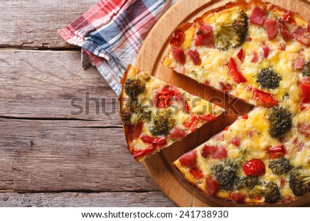 Vegetable quiche with broccoli, pepper, tomatoes close-up on the table. horizontal view from above  - stock photo