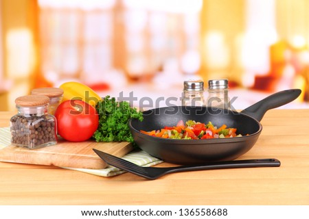 Vegetable ragout in pan,  on wooden table on bright background - stock photo