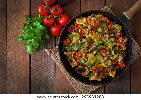 Vegetable Ratatouille in frying pan on a wooden table. Top view - stock photo