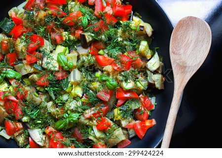 Vegetable Ratatouille in frying pan with wooden spoon. Top view - stock photo