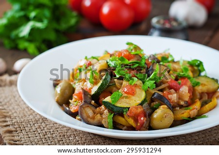 Vegetable Ratatouille in white plate on a wooden table - stock photo