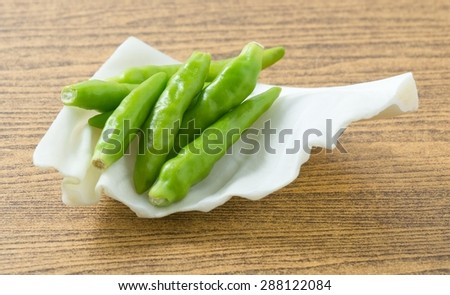 Vegetable, Raw Green Hot Chili or Chilli Cayenne Pepper on Fresh Cabbage Leaf. - stock photo