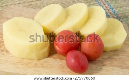 Vegetable, Raw Slice Potatoes and Fresh Tomatoes on Wooden Cutting Board. - stock photo