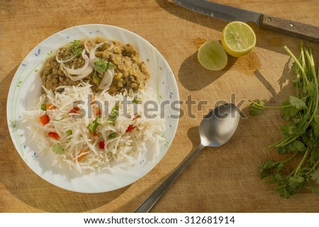 vegetable rice/ pulao and dal on cutting board with lemon and coriander leaves around. - stock photo