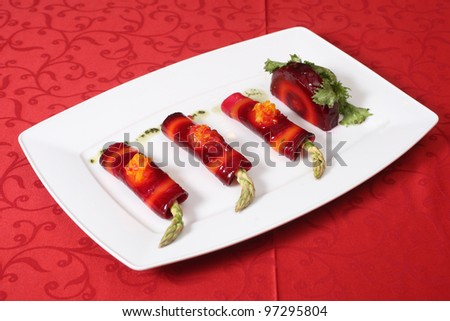 Vegetable rolls with asparagus and red beet on a white plate - stock photo