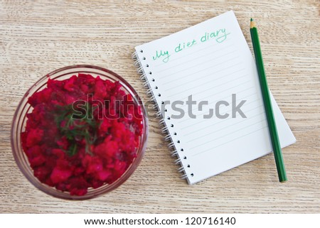 Vegetable salad, a diary diet and pencil on the table - stock photo
