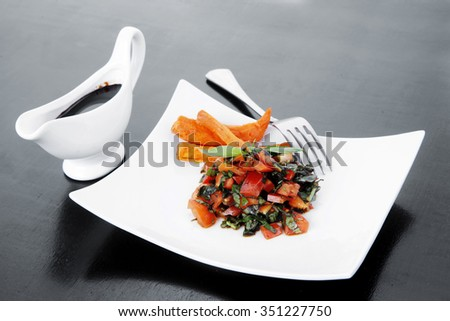 vegetable salad : cherry tomatoes and basil with sweet baked potato served on white plate with sauceboat full blask soy sauce on wood - stock photo