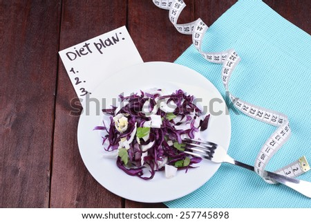 Vegetable salad for weight loss. The concept of diet and dietary food. Diet plan diet. Kitchen table, tape measure, a plate with salad, a fork and a banner with the text. Healthy food. - stock photo