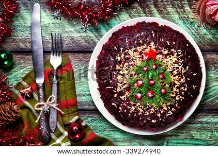 Vegetable salad from beetroot with Christmas tree decoration on the green table at New Year time - stock photo