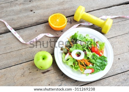 Vegetable salad,fruits and dumbbell.Health and diet concept - stock photo
