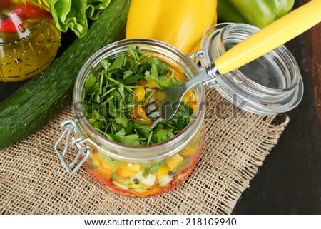 Vegetable salad in glass jar, on sackcloth napkin, on wooden background - stock photo