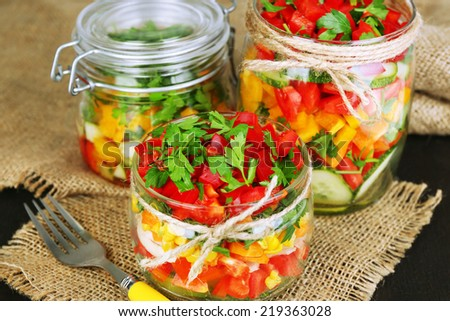 Vegetable salad in glass jars, on wooden background - stock photo