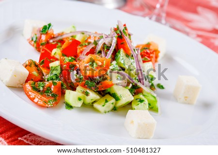 Vegetable salad with cheese on white plate