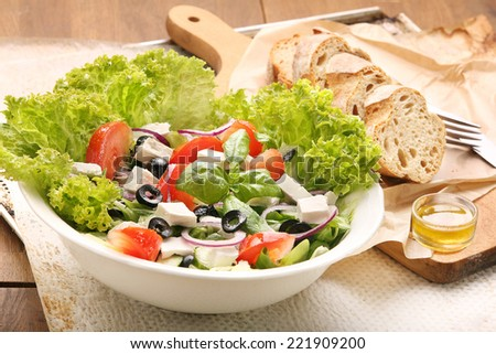 Vegetable salad with feta cheese, black olives and vinegar dip - stock photo