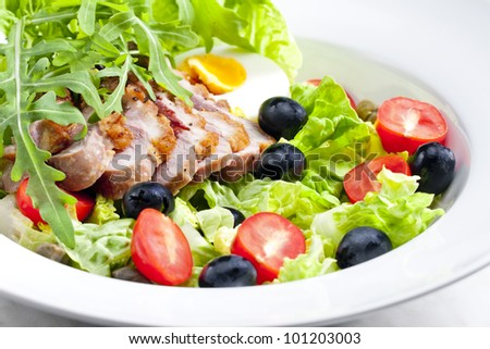 vegetable salad with fried duck breast slices and egg