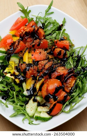 Vegetable Salad with Slices of Cucumber and Yellow Bell Pepper, Leafy Arugula, Cherry Tomatoes, Balsamic Sauce and Spices in White Bowl closeup on Wooden background - stock photo