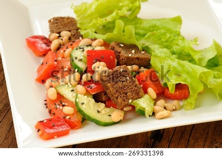 Vegetable salad with white beans, rye toasts, tomatoes, cucumber, black sesame seeds and lettuce in square plate closeup - stock photo
