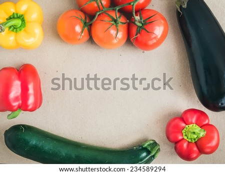 Vegetable set: ripe tomatoes, paprika, zuccini and an aggplant on a craft paper background with a copy space in the center. Top view - stock photo