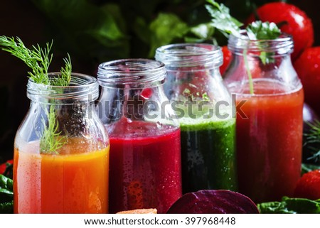 Vegetable smoothie in small bottles, dark wood background, selective focus - stock photo