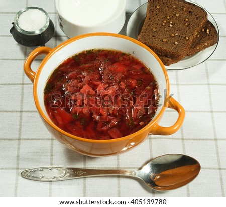 Vegetable soup (borscht).  Traditional Ukrainian soup with fresh vegetables with sour cream. Rye bread, salt and spoon. Serving on a white tablecloth. - stock photo