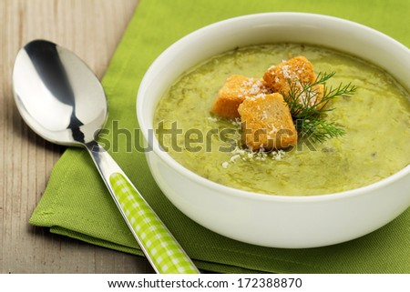vegetable soup, green napkin and tablespoon on wooden board - stock photo