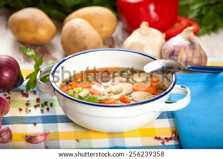 Vegetable soup in a metal bowl on a rural rustic wooden table.
